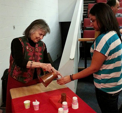Lorraine Liberty pouring a student water from her copper pitcher.