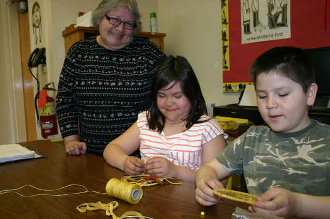 Teacher Myrtle Jamieson with Grade 3 students Kiah Monague and Kyle Monague making dream catchers to sell at the event. The  students are also making key chains.