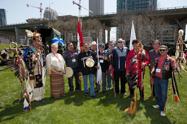First Nation Flag and Eagle Staff carriers at the April 27 commemoration of the Battle of York in the War of 1812, from left:  Emerson Benson,Myrna Watson,James Simcoe,John Snake,Mark Douglas,Bill Jamieson,Hank Monague,Brian Charles,Andrew Big Canoe, Randall May, Melvin King.   – Photo by Keesic  Douglas,  Chippewas of Rama FN