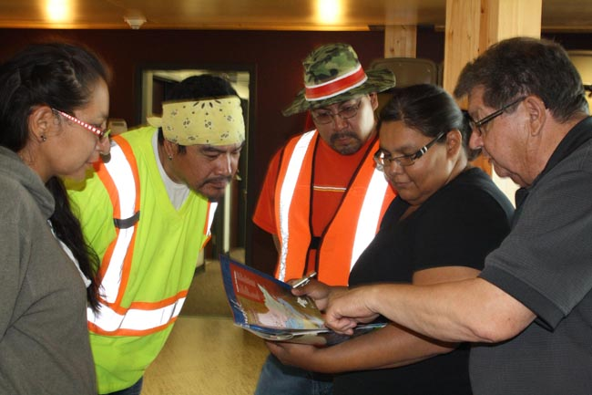 Unity Walkers with Restoration of Jurisdiction director Mike Restoule take a look at the Anishinabek Nation map in the centre of the 19th Annual Great Lakes Pow-wow Guide.             – Photo by Monica Lister