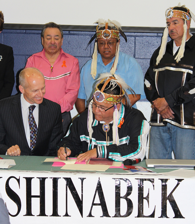 Grand Council Chief Patrick Madahbee signs protocol agreement between Anishinabek Nation and Cancer Care Ontario, with CCO president and CEO Michael Sherar, front left, Ontario Regional Chief Stan Beardy, Anishinabek Deputy Grand Chief Glen Hare, and Lake Superior Regional Grand Chief Peter Collins looking on.      – Photo by Maurice Switzer