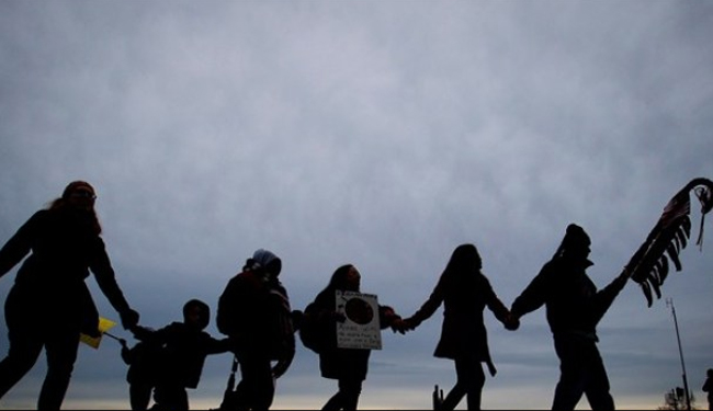 First Nations Idle No More protesters hold hands during a demonstration at the Douglas-Peace Arch crossing near Surrey, B.C.    – Photo by Darryl Dyck, Canadian Press