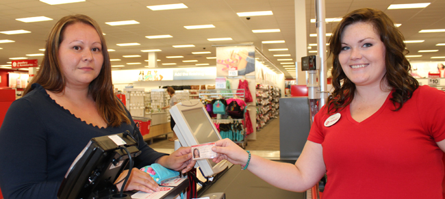 Nipissing First Nation citizen, Theresa Stevens, presents her Indian Status Card to Target employee Laura Dawkins.  – Photo by Marci Becking