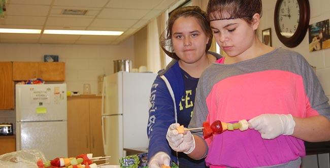 Grade 7 students Amber Chiblow and Heidi Eshkakogan preparing for school-wide sale of fruit kabobs and veggie trays to raise money for the Canadian Diabetes Association.
