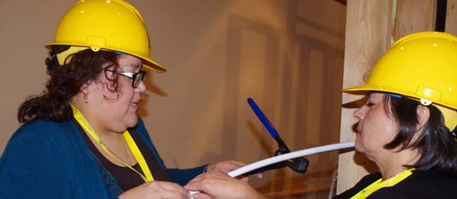 Atikameksheng Anishnawbek contestants Cheryl Nebenionquit and Norma Petahtegoose installed plastic pipe lines during the third Builder's Challenge at the 12th Annual First Nations Northern Housing Conference, held Feb. 11-13 in Thunder Bay.