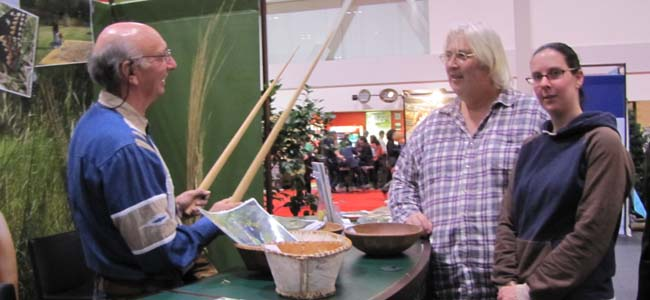 Jeff Beaver shows harvesting sticks for wild rice to Scout leader Mike Bozek and daughter Kaley Cartwright at Toronto Sportsmen's Show.