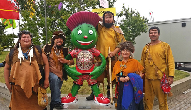 Global Savages posing with Commonwealth Games mascot, Clyde.  From left:  Jessica Wilde-Peltier as Giizhigo Kwe (Sky Woman), Joe Osawabine as Debajehmud, Clyde,   Josh Peltier as Maudjeekawis,  Jeanette Corbiere-Lavell as Nokomis and Bruce Naokwegijig as Chibiabos.