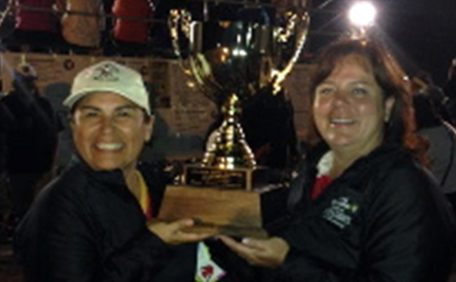 Jane Commanda and Monique Sawyer of Nipissing First Nation hold the Lori (Scoop) Johnson Memorial Trophy for winning the 2014 Masters Women's Division at Canadian Native Fastball Championships.