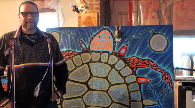 """Nipissing First Nation artist Donald Chretien beside his work """"The creation story""""."""