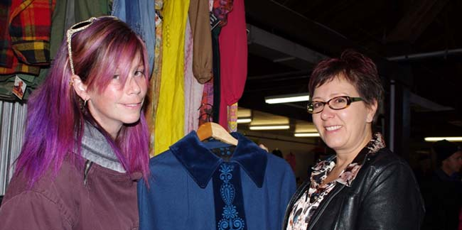 Mustang Sally Vintage owner Denise Atkinson, right, displays one of her vintage dresses to a customer on a Saturday morning at the Thunder Bay Country Market.