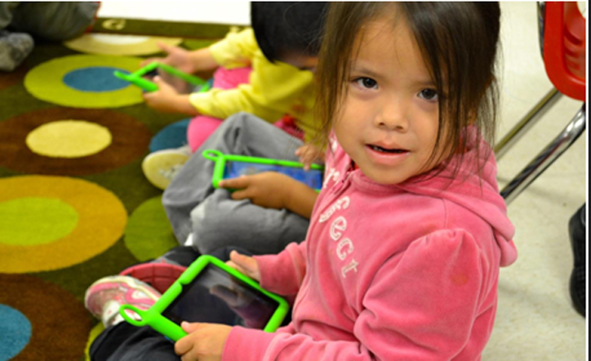 A young student in Sagamok Anishinawbek explores an One Laptop Per Child Canada tablet.