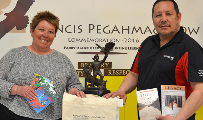 Roxane Manitowabi and Roger Chum of the Ontario Native Education Counselling Association (ONECA) with thank-you gifts for donors to the Pegahmagabow monument. – Photo courtesy of Sculpture by Tyler Fauvelle, Lively, Ontario.