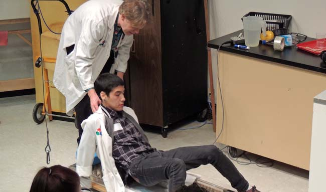 Zeke McLeod laying on a bed of nails- science educator Martin Fischer behind him.