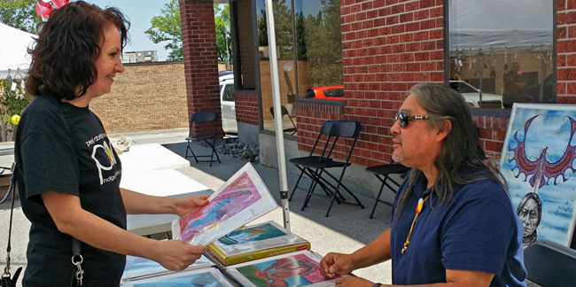 A Peel Aboriginal Network volunteer speaks with artist Jay Bell Redbird at The Gathering in Mississauga, June 6.