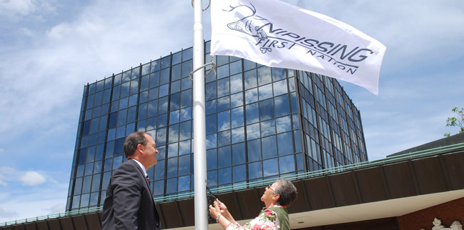 North Bay mayor Al McDonald and Nipissing First Nation Chief Marianna Couchie raise Nipissing First Nation's flag together at city hall on June 19 for Aboriginal Day.
