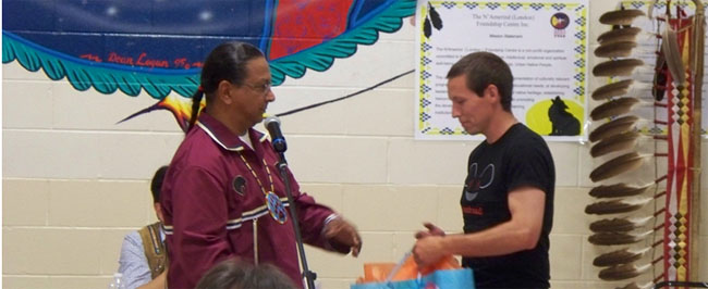 Brett Watson receives congratulations, gift and handshake from Brian Hill, President of N`Amerind Friendship Centre.