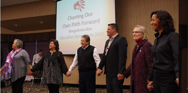Regional Chief Isadore Day and Indigenous and Northern Affairs Minister Carolyn Bennett, second and third from right, participate in an opening exercise on the first day of the Chiefs of Ontario Education Symposium in Thunder Bay.