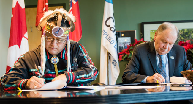 Grand Council Chief Patrick Madahbee and Niagara College President Dan Patterson renew the Niagara College - Anishinabek Educational Institute's partnership on Dec. 11, 2015 in Niagara Falls.