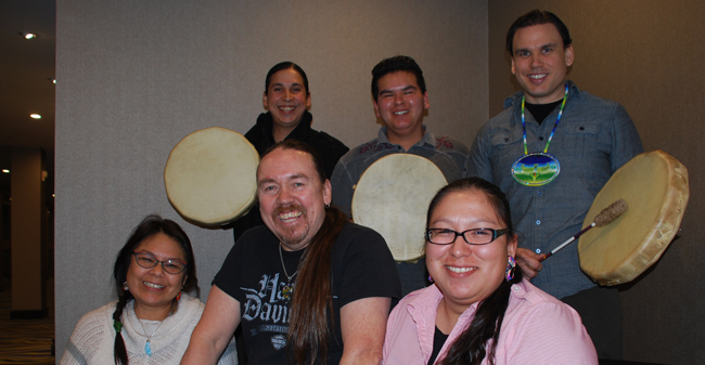 Drummers honour the information session of the Anishabek Nation Education Agreement: from left (front)Annette-Ashawasega Cristo of Henvey Inlet, Perry McLeod-Shabogesic, Nipissing, and Crystal Kimewon, Wikiwemkong; Bryden Kiwenzie of Neyaashiinigaming First Nation (Cape Crocker), Bradley Shawanda of Sheguindah, and Brad Robinson, Oneida Nation of the Thames.
