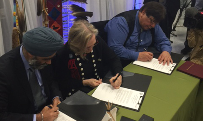 National Defence Minister Harjit S. Sajjan, Indigenous and Northern Affairs Minister Carolyn Bennett and Kettle & Stony Point Chief Thomas Bressette at the final settlement signing after 74 years.