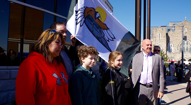 Fort William Chief Peter Collins, left holding flag, Thunder Bay Mayor Keith Hobbs and the youth who raised the Fort William First Nation flag gather for a photo during the May 2 flag-raising ceremony at Thunder Bay City Hall.