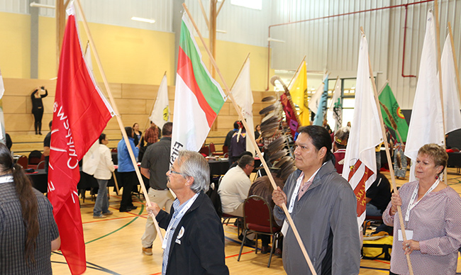 Chippewas of Rama Chief Rodney Noganosh carries his community's red flag with the other Chiefs in Assembly.