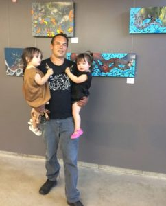 Shaun Hedican with his two daughters at his art exhibition in Thunder Bay.