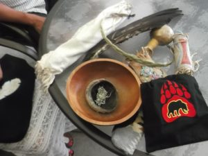 ceremonial pipe in pouch, eagle feather, rattle, medicine pouches, black medicine pouch with Bear, symbol of her Cayuga clan.  Front left; smudging bowls with sage.