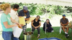 Debajehmujig's Joseph Osawabine and Ashley Manitowabi check out a couple of beehive frames during a Roots to Harvest workshop at the Wee Tum Ma Keh Wina Food Symposium on Aug. 24 at Camp Duncan near Thunder Bay
