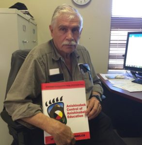 Biigtigong Nishnaabeg Chief Duncan Michano with a Say Yes to AES  > folder calling for Anishinabek Control of Anishinabek Education.